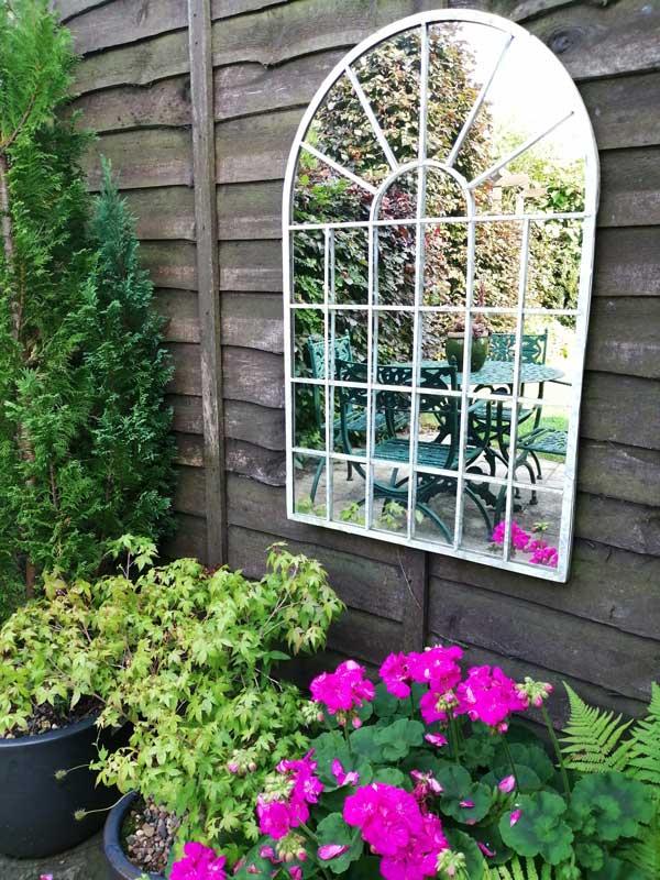 Mirror on fence showing reflection into Fredas Garden